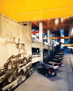 """Not content to just build a regular parking lot behind the Himalayan facade, Ingels created a high-ceilinged, five-story, concrete-and-steel """"car cathedral—to celebrate car culture."""" Throughout, the French artist Victor Ash varnished the concrete walls with gray-on-gray murals of wild animals—a wolf, a moose—standing atop piles of wrecked automobiles."""