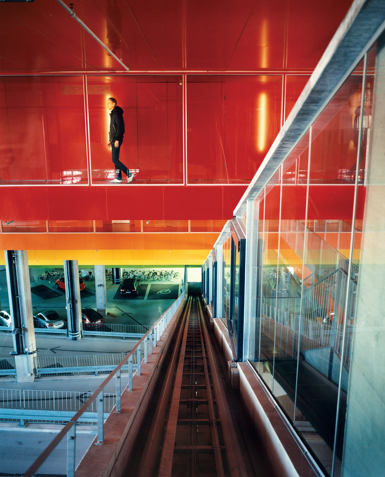 "The halls connecting the garage to the residences are covered in brightly painted aluminum treatment associated with cars, not buildings. The colors move, symbolically, from earth to sky: green, yellow, orange, dark orange, hot pink, purple, bright blue. ""Buildings are never brightly colored,"" says Ingels, explaining the thinking behind this stepladder rainbow, ""but cars often are.""  Photo 9 of 20 in Mountain Dwellings Urban Development in Copenhagen"