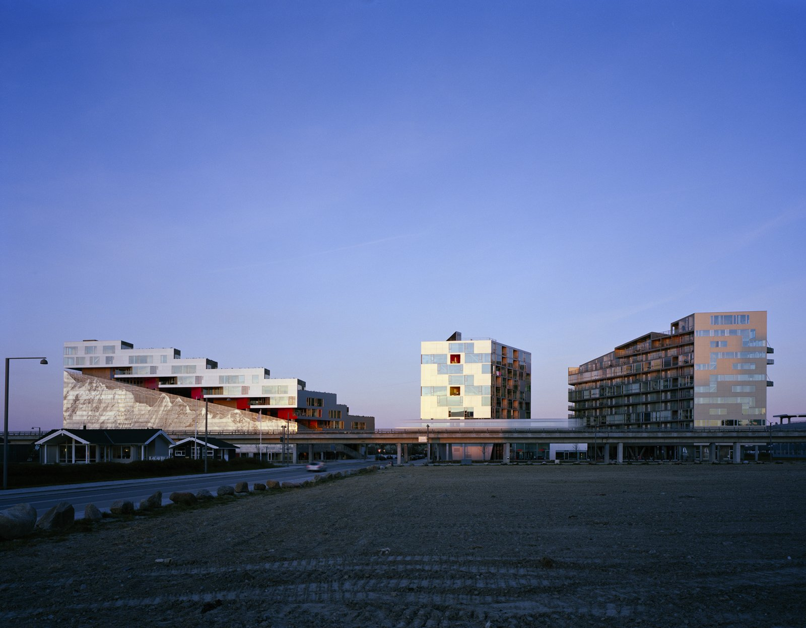 The VM Houses (the two buildings on the right) opened in Ørestad in 2005, with the Mountain Dwellings (left) following in 2008. Up next in the neighborhood: The firm's BIG House (or Figure Eight building) is scheduled to be completed in 2010.  Photo 13 of 20 in Mountain Dwellings Urban Development in Copenhagen