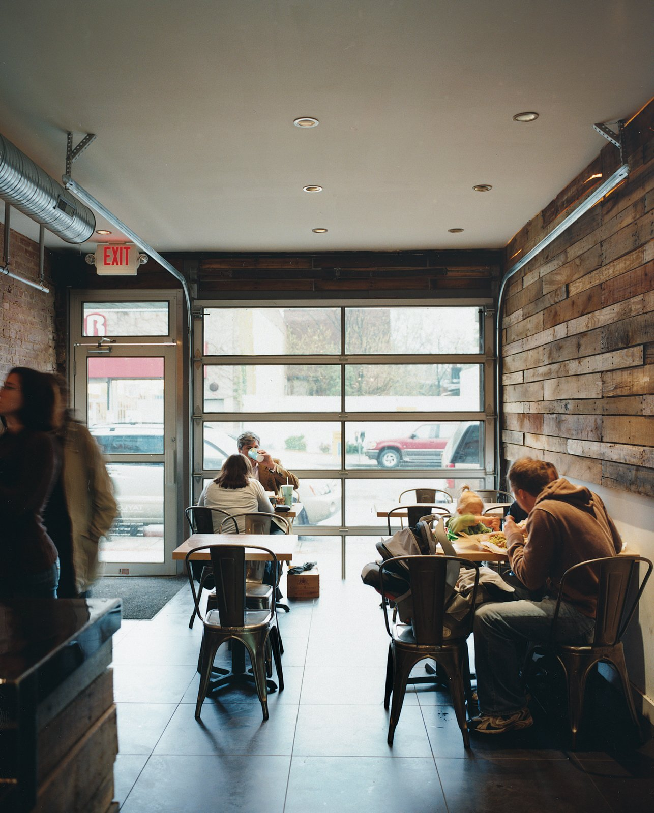 The roll-up doors on the facade give Taylor Gourmet an outdoor feel while the wooden walls made of recycled shipping pallets offer a textured, rustic feel.  Photo 9 of 13 in Hoagies' Heroes