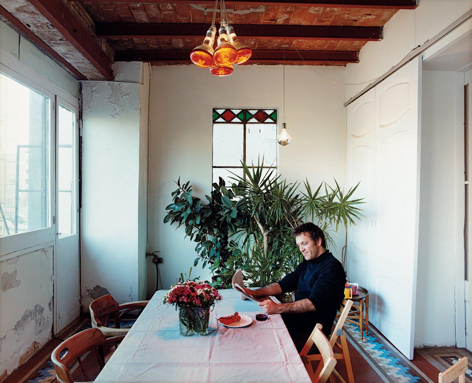 """Dining Room and Pendant Lighting The couple took down a wall to create the open kitchen and lounge space where Tham and Hanna play. Wooden panels that aped a Swiss chalet also came down out of the """"interior patio,"""" making the dining room more palatable.  Photo 3 of 6 in Renovating Old and New in Barcelona"""