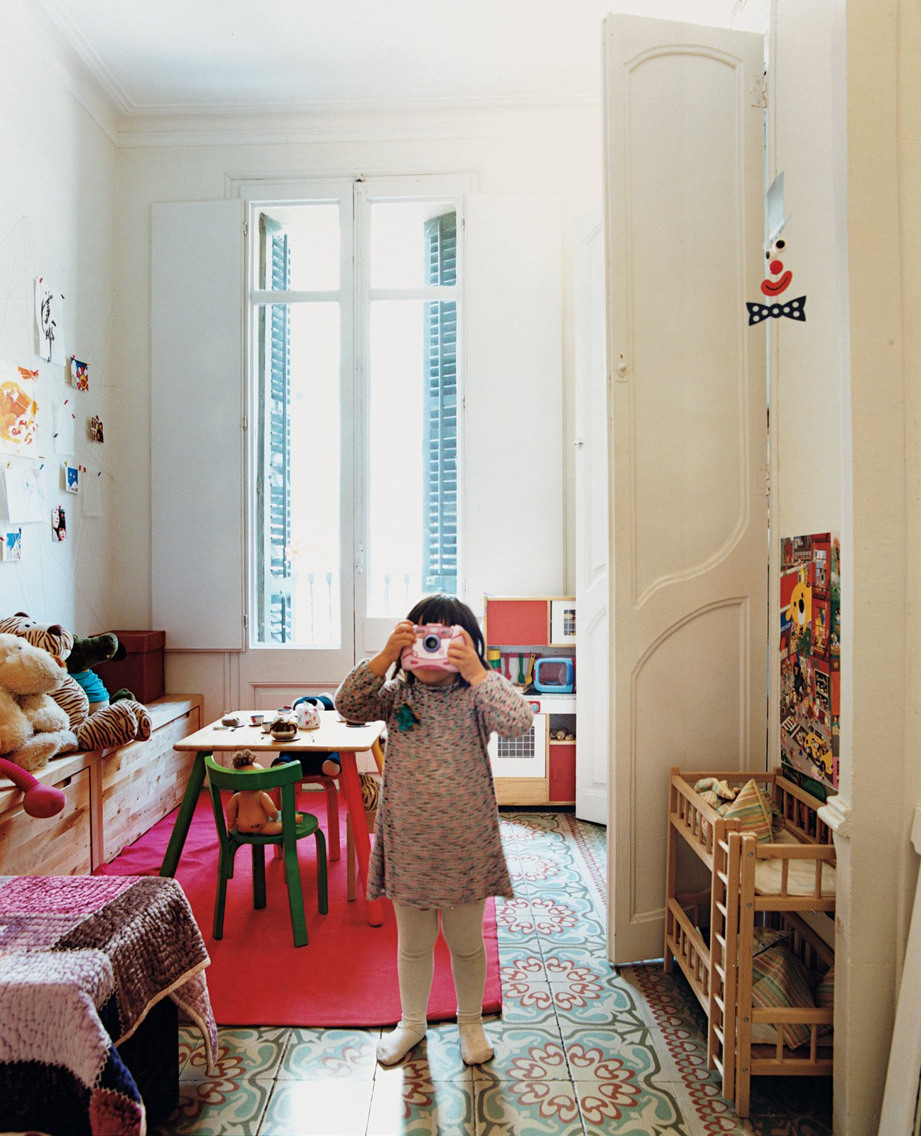 """Kids Room and Bedroom Room Type """"It's typical for Barcelona buildings from this period that the bedrooms are divided with decorative plaster columns and a cornice to create a curtained-off alcove for the bed, separating it from the more public part of the rest of the room. We opened up our bedroom, but we conserved that feature in Hanna's room, and now every morning she wants to play dress-up.""""  Photo 4 of 6 in Renovating Old and New in Barcelona"""