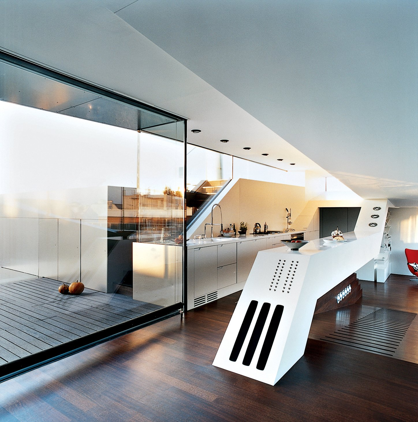 "The ""culinary cockpit"" (a.k.a. the kitchen) stands at the center of the apartment on a raised platform. A long, white slanted counter contains hi-fi speakers and a BUS-system panel of 18 buttons for controlling lights, curtains, heating, ventilation, etc.  Photo 7 of 16 in The Penthouse Has Landed"