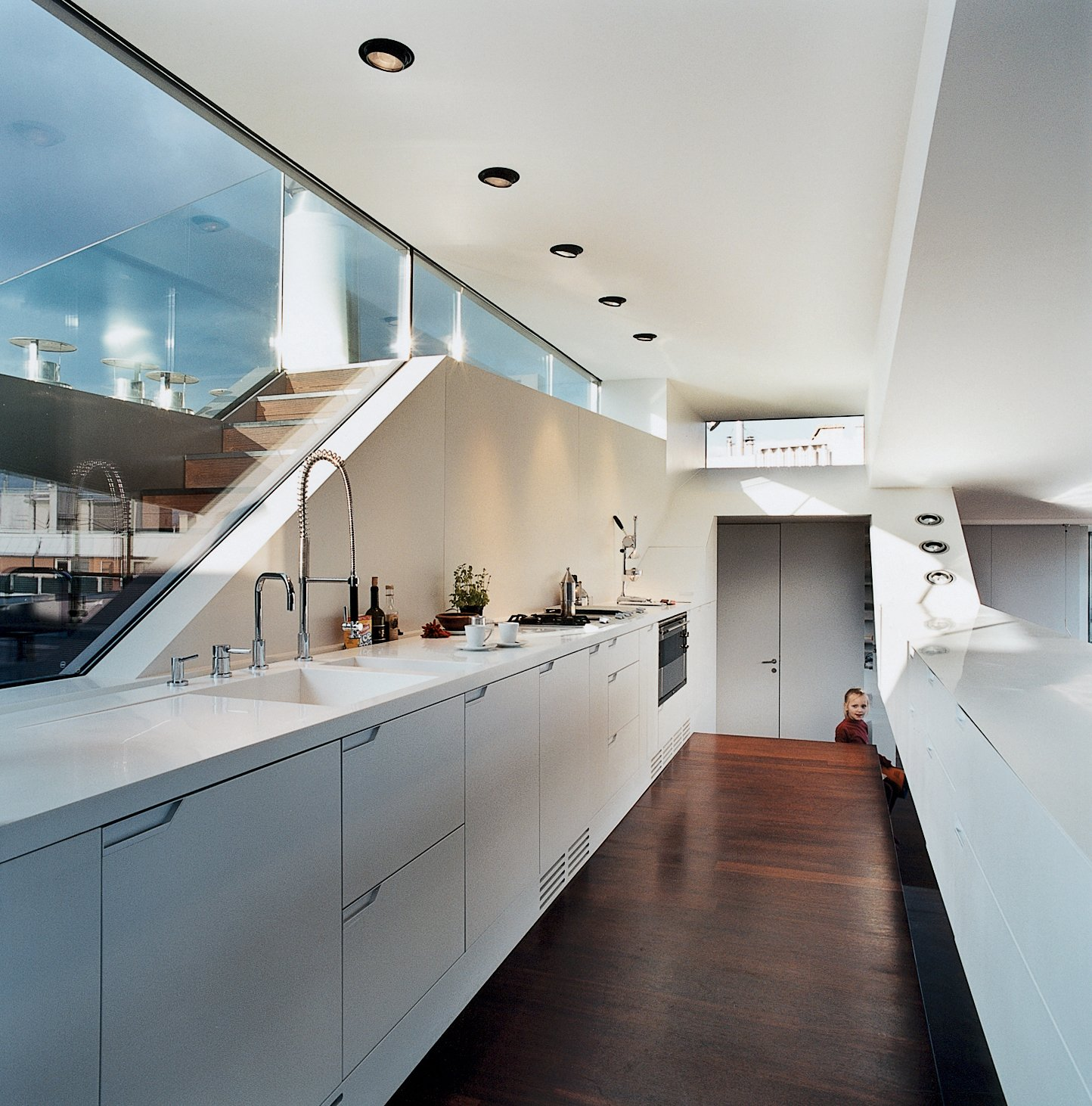 The kitchen window looks out to stairs that lead up to a small roof terrace. The kitchen faucet is byDornbracht. The recessed lighting is by Guzzini.  Photo 9 of 16 in The Penthouse Has Landed