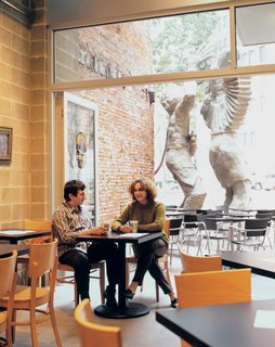 Architect Dutch MacDonald and developer Eve Picker relax at the Pittsburgh Presse Deli in the building's ground-floor storefront. Designed by MacDonald's Edge Studio, the restaurant serves gourmet panini six days a week.