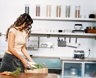 "Mandi Rafaty's girlfriend, Yoly Guerra, unpacks groceries in preparation for dinner. The kitchen cabinets are off-the-shelf models from IKEA, and all knives are stored on a space-saving magnetic hanging holder on the wall. Two floating, open shelves above the Tag Front cast-concrete sink and Frigidaire dishwasher act as home base for plates and dishes, while a convection oven by Sharp, Turbo Air commercial-grade refrigerator, and two glass cabinets finish off the kitchen. ""It's all about creating these setups that don't visually make the space feel smaller than it already is,"" Mandi says."