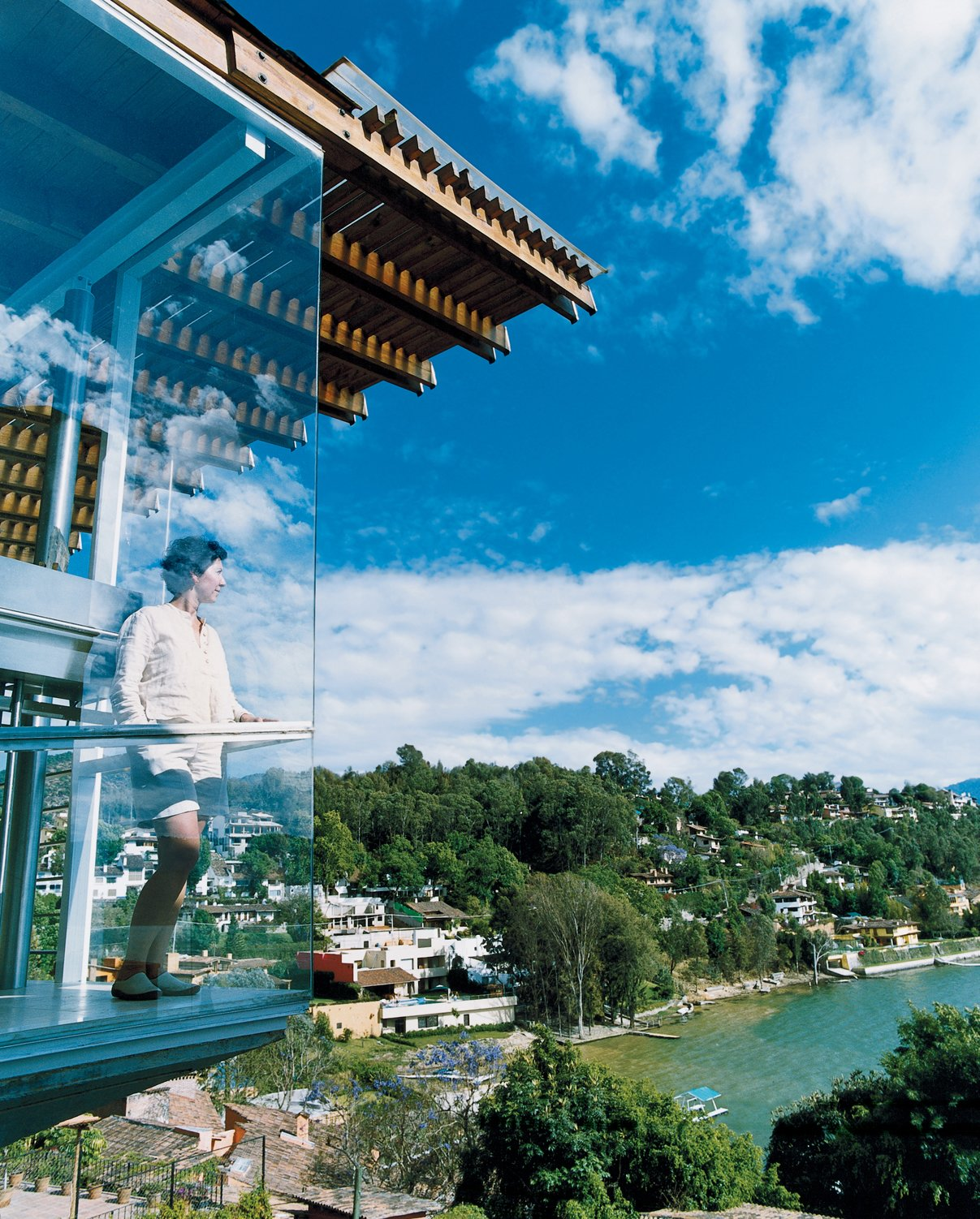 For his lakeside retreat just outside Mexico City, architect Bernardo Gomez-Pimienta designed everything from the house to the chairs to the china. Here, his wife, Loredana Dall' Amico, checks out the view from the balcony.  Photo 1 of 10 in Reflections on a Lake
