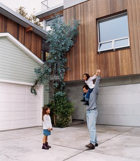 The architect with his daughters. The redwood strips on the new house were purposely cut to the same width as the horizontal wood siding on the old house to create visual harmony between the two.