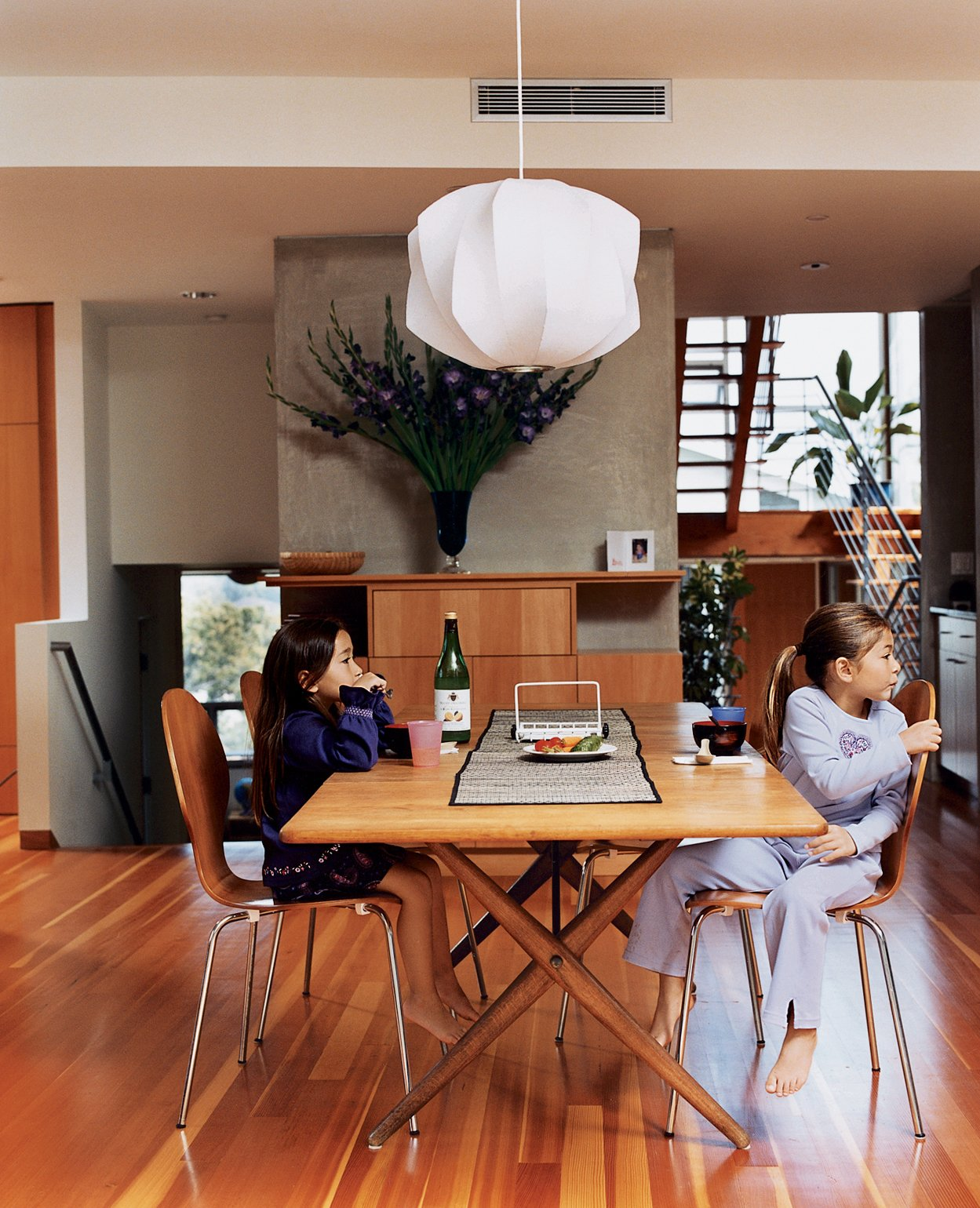 Dining Room, Pendant Lighting, Chair, Table, and Medium Hardwood Floor Kalia and Olivia in the dining room (the Danish dining table was acquired by Jesse's parents in the mid-'70s, the dining chairs are by Arne Jacobsen, and the light fixture is by George Nelson).  Ways to Decorate with Arne Jacobsen Furniture by Erika Heet from Two Houses Are Better Than One