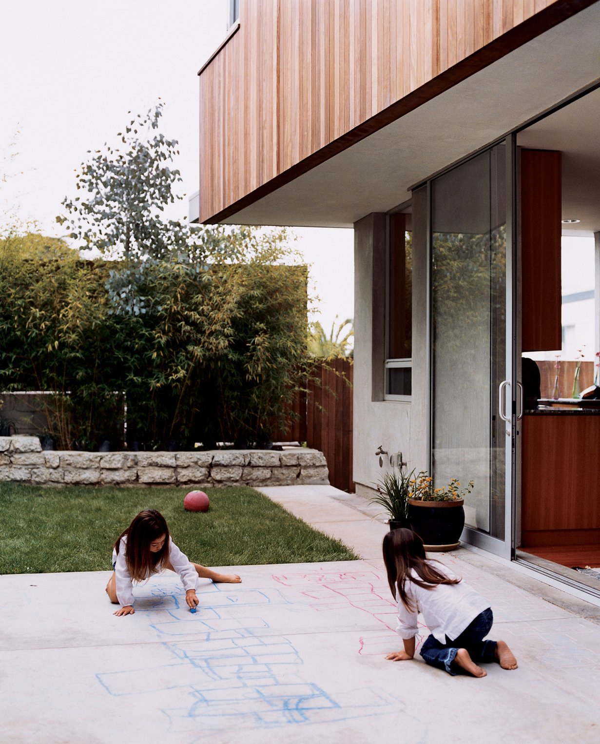 """Outdoor, Grass, Back Yard, Concrete Patio, Porch, Deck, and Large Patio, Porch, Deck Kalia and Olivia enjoying the outdoor space. Kalia's favorite part of the house? In her own words, """"I like the backyard where we play soccer, hopscotch, and jump rope and draw and have picnics."""" 'Nuff said.  Photo 13 of 13 in Two Houses Are Better Than One"""