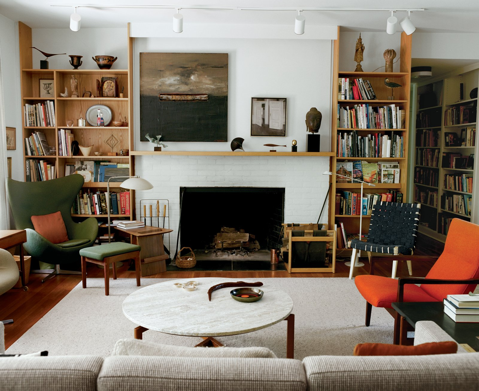 Living Room, Standard Layout Fireplace, Ceiling Lighting, Rug Floor, Coffee Tables, Sofa, Chair, Shelves, Bookcase, Wood Burning Fireplace, and Track Lighting In legendary designer Jens Risom's home, the painted white brick fireplace is flanked by wood bookshelves that join to form a mantle.  Photo 16 of 20 in 20 Modern Living Rooms from Fascinating Risom