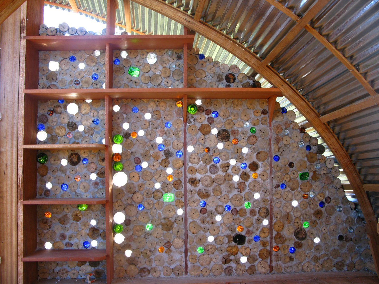 Nonn and Martin collected bottles from the roadside for use in the walls. The bottles let colored light filter into the cabana, and passing breezes create sound effects on the mouths of the bottles.  Photo 3 of 13 in Venezuela's Eco Cabanas
