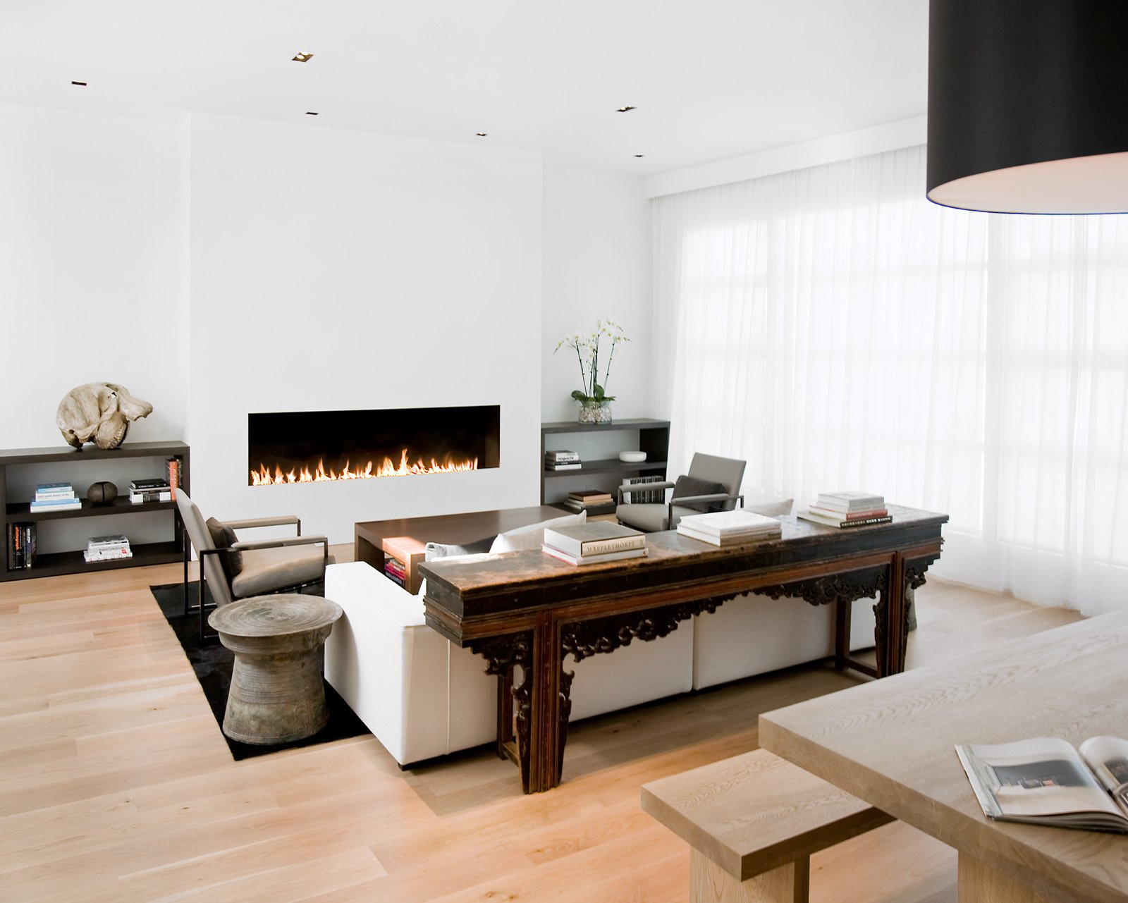 The living room and dining room were originally separated by a central fireplace, which Hollis removed to create this great room. She installed a custom eight-foot-long open gas fireplace in the living room (equipped with sensors that automatically turn it off when someone gets too near to the flames).Photo by   Ben Mayorga Photography  97+ Modern Fireplace Ideas