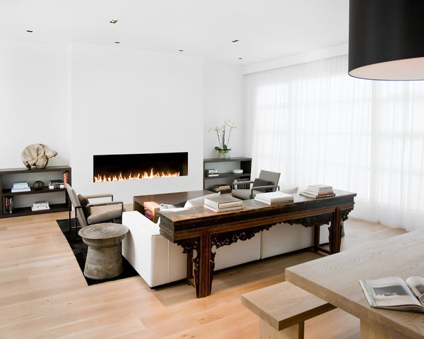 The living room and dining room were originally separated by a central fireplace, which interior designer Nicole Hollis removed to create this great room. She installed a modern, custom eight-foot-long open gas fireplace in the living room, equipped with sensors that automatically turn it off when someone gets too near to the flames.