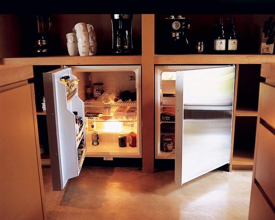 """To help keep the house free of clutter, the full-size refrigerator was hidden in a basement utility room. An unobtrusive three-foot-tall fridge and matching freezer—made by Sub-Zero—were tucked beneath a kitchen countertop. """"There are so many more options with refrigeration, and under-the-counter is really great,"""" says Vetter. """"You free up space and don't have this big, clunky thing sitting there."""" www.subzero.com  Photo 7 of 8 in Four Walls and a Screw-Top"""