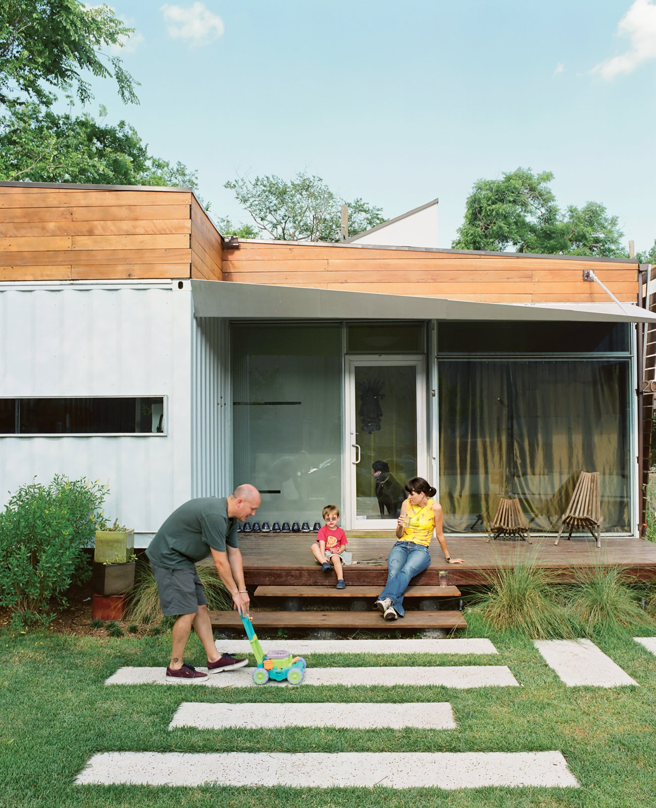 """Exterior, House Building Type, Shipping Container Building Type, Metal Siding Material, and Wood Siding Material One of the main draws of Kevin Freeman and Jen Feldmann's house is its connection to the neighborhood, which is why the front porch was a must. """"Homes that have a door but no outside space say, 'I'm not interested in you,'"""" designer Christopher Robertson explains. """"This says, 'I'm here to be part of the community.'""""  Photo 1 of 22 in The Shipping Muse"""