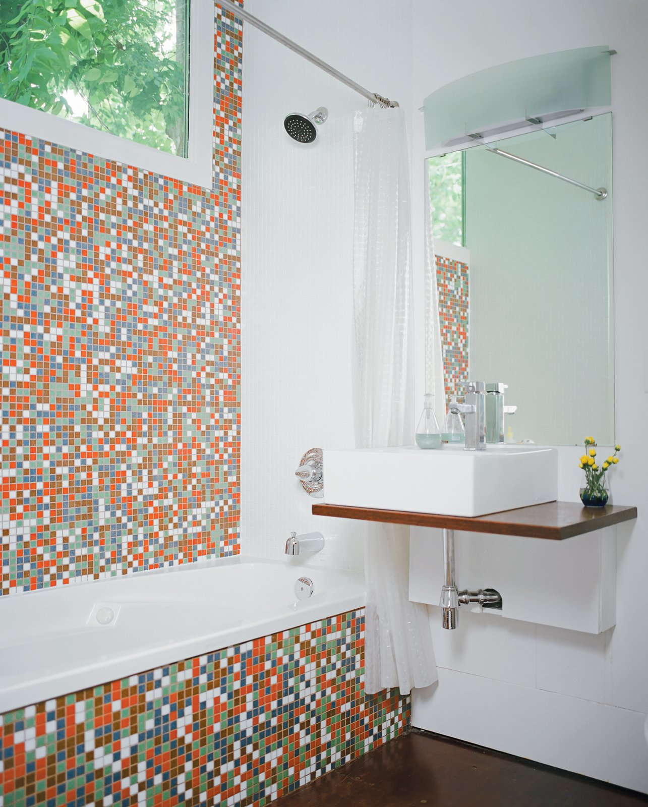 Bath, Mosaic Tile, Wall Mount, and Vessel Robertson--with the help of developers Katie Nichols and John Walker, who were heavily involved in the design process--finished the guest bathroom with Modwalls tiles and a sink they found on eBay. They used a piece of marine plywood, leftover from building the front-porch steps, to create a counter on which the sink could sit--and where the family can rest their toothbrushes. To the right of the sink is a Toto dual-flush toilet, which is great for conserving water but has proven problematic for toilet training, as American potty seats aren't designed to fit these Japanese basins.  Best Bath Vessel Mosaic Tile Photos from The Shipping Muse