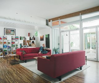 """The open-plan living spaces act like a """"giant kitchen"""" that invites guests to mingle throughout the house. The white rug anchors the living room furniture, which includes two red couches from Room and Board and a coffee table and end tables that were thrift-store finds.  Roberston opted for commercial storefront doors over sliding glass ones for the back of the house. """"It's the least expensive way to get a wall of glass,"""" he says. The only drawback: The doors automatically lock when they close so Freeman and Feldmann have to be sure to always have keys on hand."""