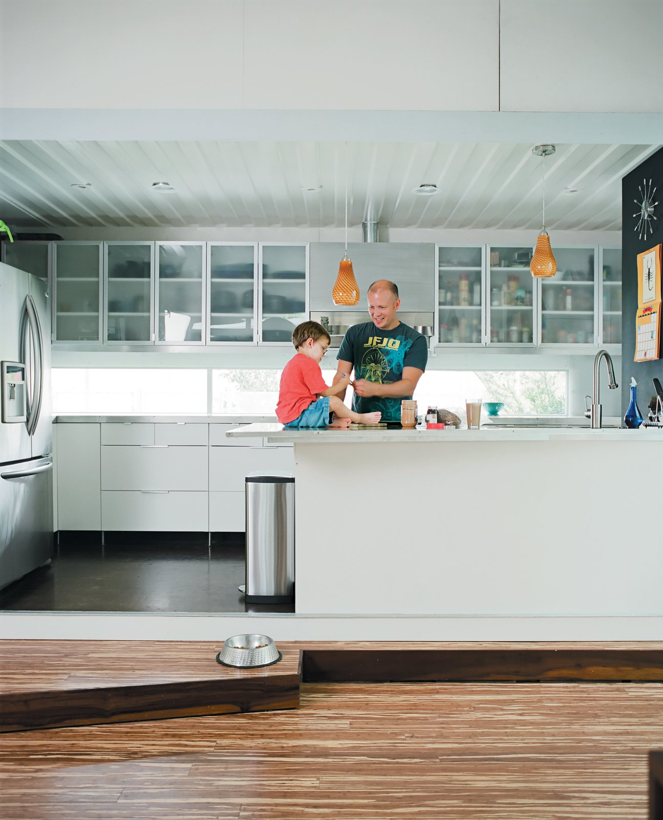 Kitchen and White Cabinet In the kitchen proper, Freeman fixes a snack while son Eli plays on the counter, one of his favorite spots in the house, second only to the kitchen steps.  Shipping Containers by Dwell