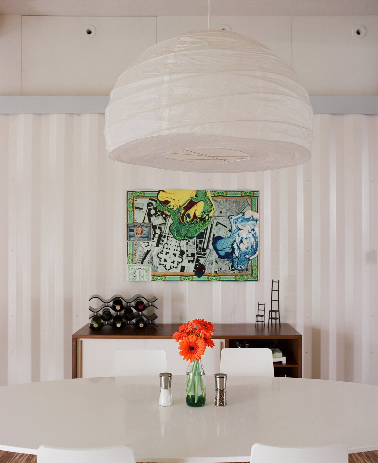 """Dining Room and Pendant Lighting For the dining room, Freeman and Feldmann swapped their tiny table for developer John Walker's larger one since he was moving into a smaller space. They topped it with a $12 pendant lamp from Ikea and finished the """"room"""" with a counsel from West Elm.  Photo 13 of 22 in The Shipping Muse"""