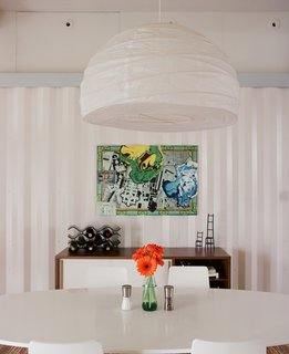 """For the dining room, Freeman and Feldmann swapped their tiny table for developer John Walker's larger one since he was moving into a smaller space. They topped it with a $12 pendant lamp from Ikea and finished the """"room"""" with a counsel from West Elm."""
