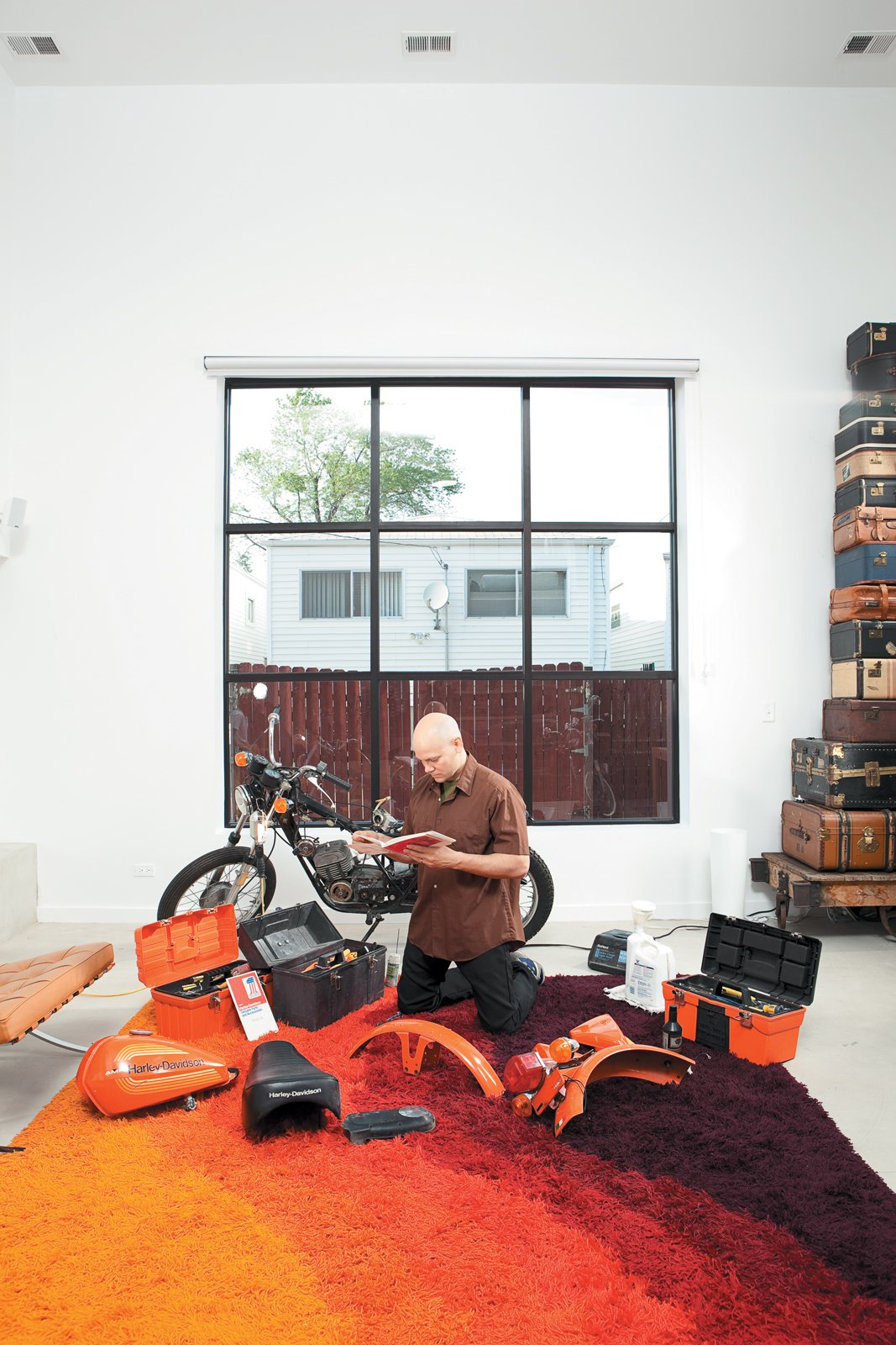 Living Room and Rug Floor In the light-flooded living room, Hernandez does a little work on a 1976 Italian-made Harley-Davidson SXT125.  Photo 9 of 10 in The Brick Weave House in Chicago