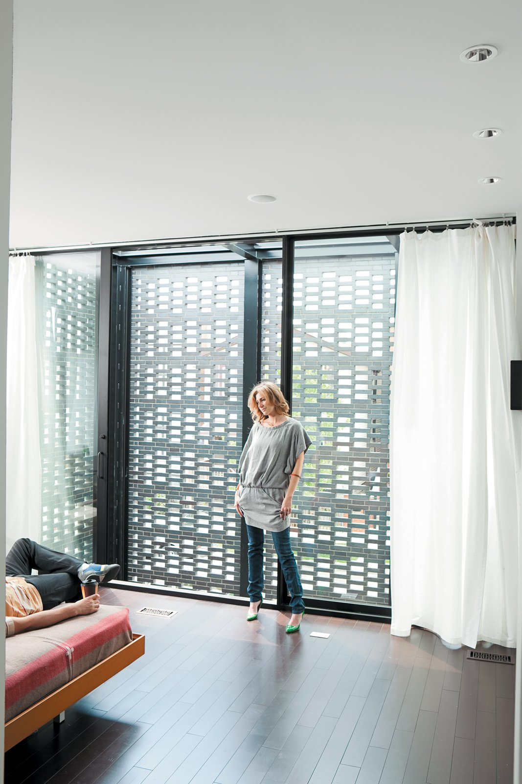 Bedroom, Bed, and Dark Hardwood Floor In the master bedroom, the couple enjoy the ample natural light that filters through the brick screen.  Photo 6 of 10 in The Brick Weave House in Chicago