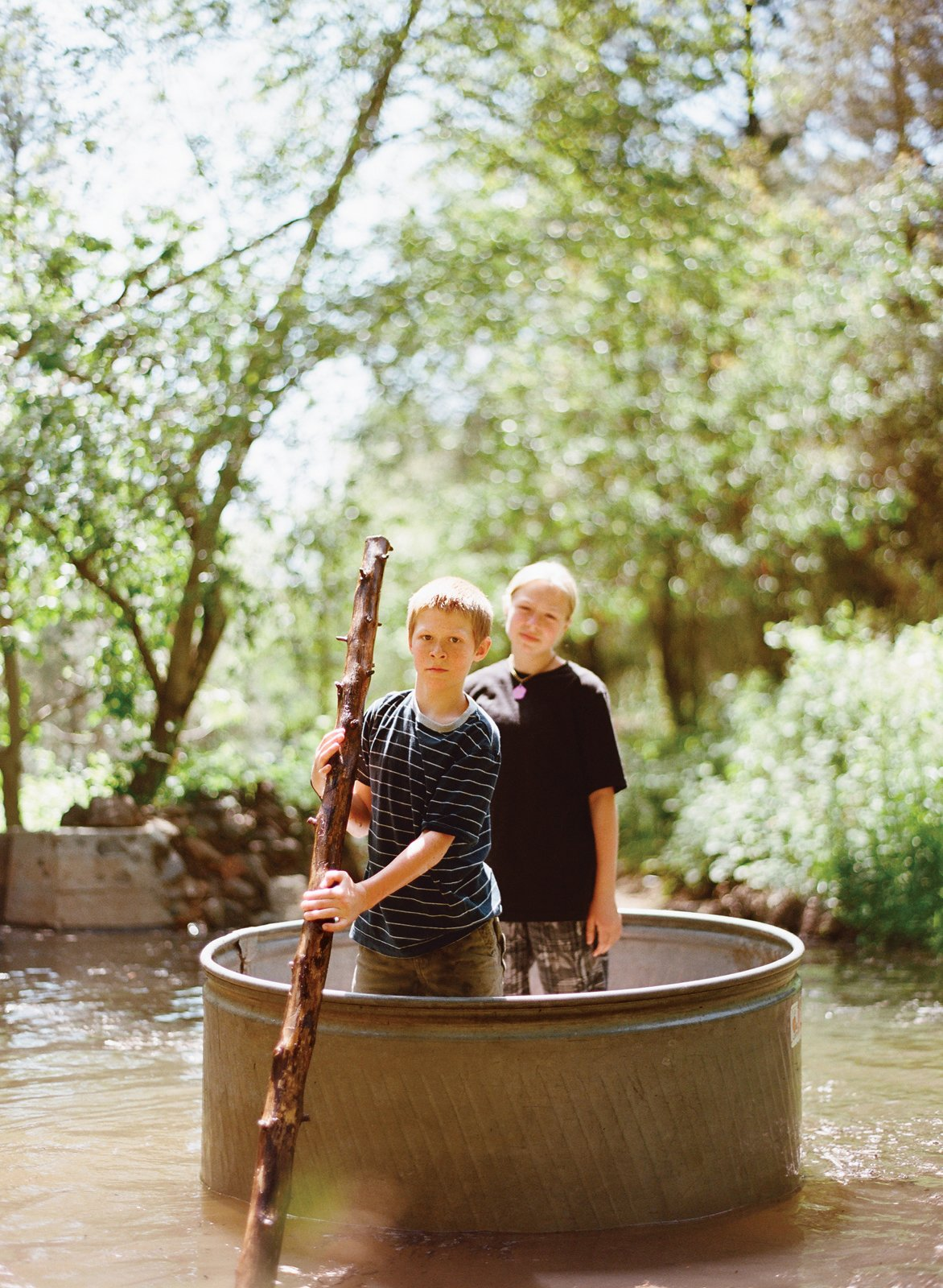 Outdoor Dylan, 10, and Zoe, 13, have a lazy float down the creek, Huck Finn–style, in a steel horse-watering tank.  Photo 3 of 13 in Diamond in the Rough (and Ready)