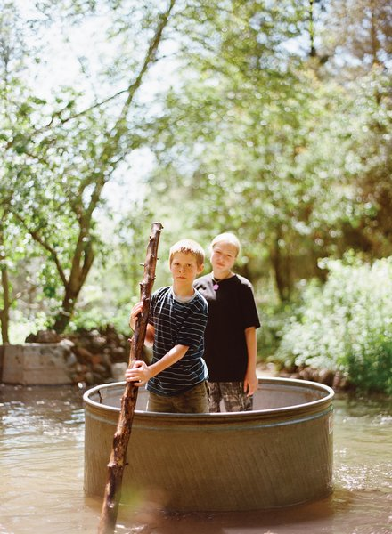Dylan, 10, and Zoe, 13, have a lazy float down the creek, Huck Finn–style, in a steel horse-watering tank.