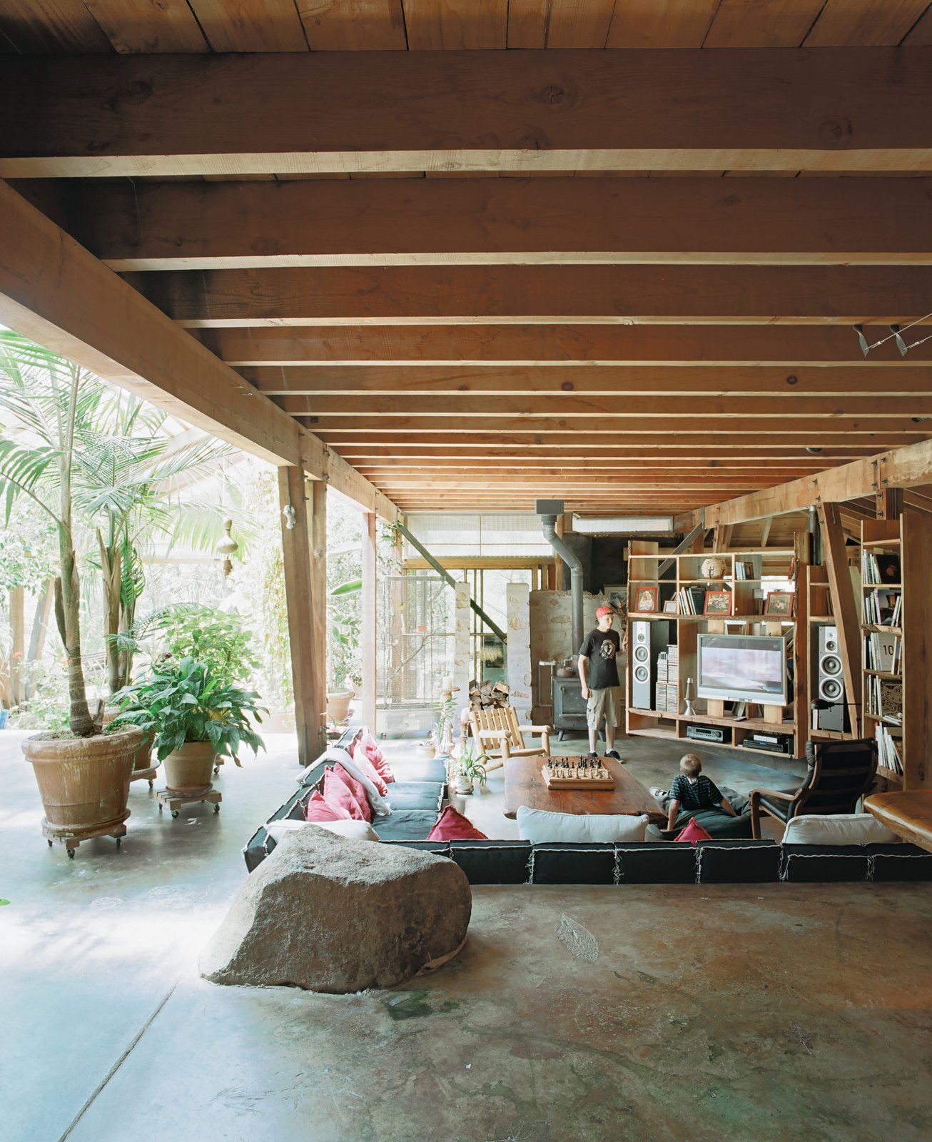 Living Room and Concrete Floor Rocks dug up during construction were saved and incorporated into the poured-concrete floors and walls. Hydronic heating coils in the floor are augmented by a wood stove during the damp winters.  Photo 6 of 13 in Diamond in the Rough (and Ready)