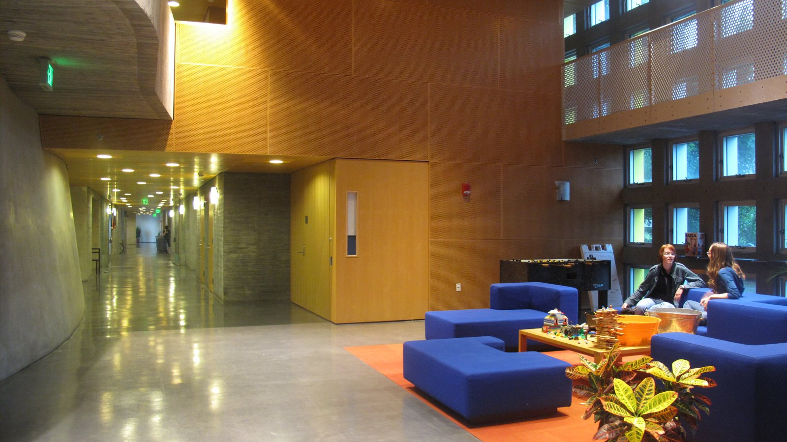 "Renee and Amanda chat in the Simmons mail room, which is also the lobby and used as a meeting place. You can see three levels of porosity -- perforated wood paneling, metal overhead railing, and windows in the concrete walls.  Photo 3 of 8 in ""I Live in a Steven Holl"""