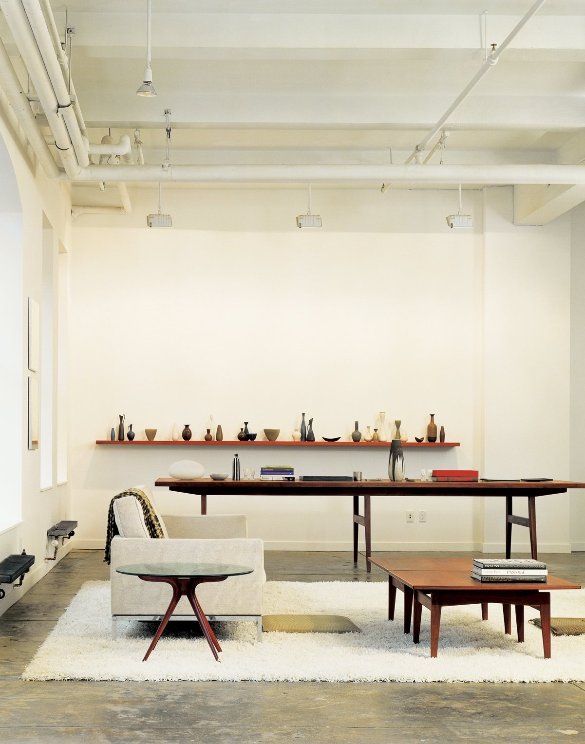 "The oversize conference table in Bob Weinstein's live/work loft (like the cocktail table in the foreground) was designed by Jens Risom, and, he says, ""supposedly came from the conference room of the Kinney Shoe Corporation."" Weinstein uses the table to display part of his Scandinavian pottery collection.  Loft from A Mid-Century Manhattan Loft"