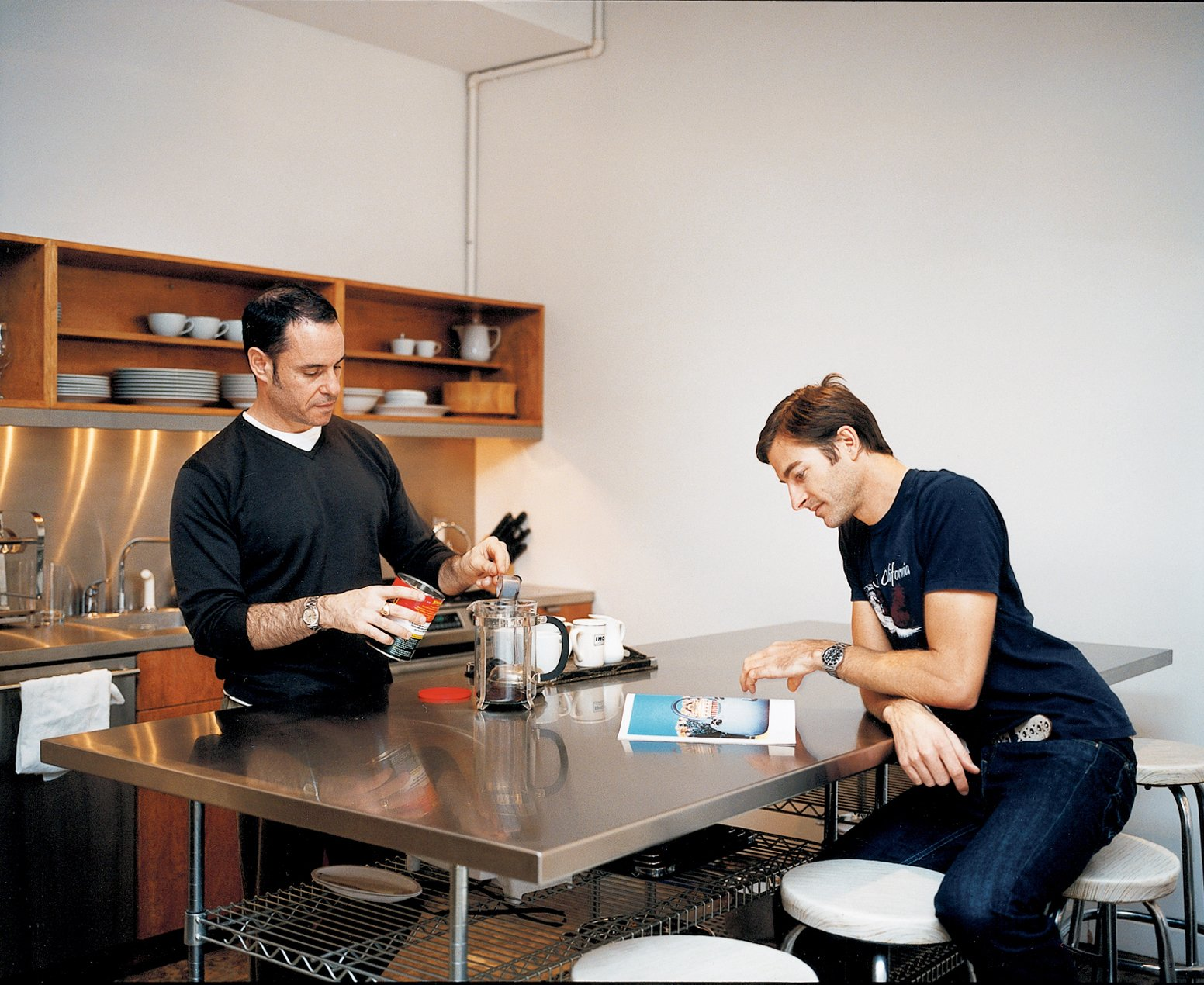 Weinstein and partner Eric Hensley at the stainless steel work table in the kitchen. The table, pantry doors, and sink backsplash are all made from simple wood forms the architects had wrapped by a metal fabricator—something anyone can do.  Photo 2 of 6 in A Mid-Century Manhattan Loft
