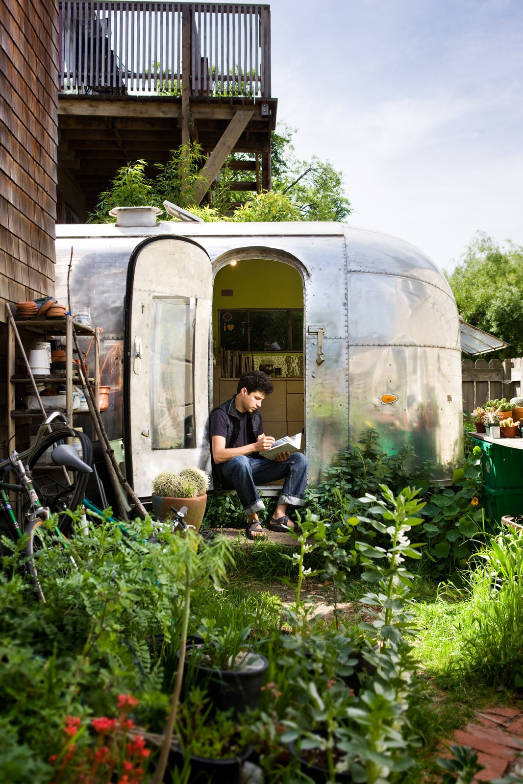 """Exterior, Airstream Building Type, Metal Siding Material, and Metal Roof Material The Airstream is tucked into the back garden of a Berkeley co-op.  Having a garden at my footsteps and chickens just over the fence make it feel peaceful and private.  Search """"jansen co my mug espresso saucer"""" from The Airstream Life"""
