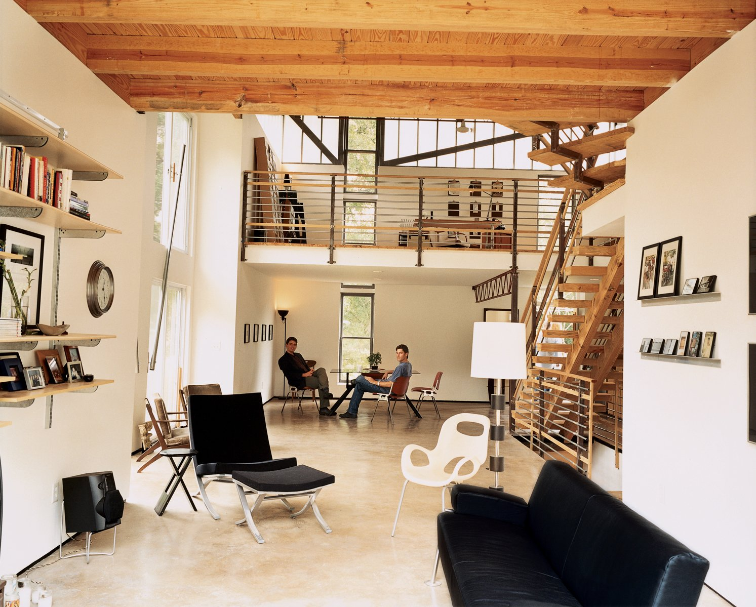 The house is designed like an urban loft. Even elements such as the staircase and second-floor railings are almost transparent, so natural light floods the structure from dawn to dusk. Moseley's friend David W. Prasse (right) and designer Scott Ball take it all in.  Photo 1 of 8 in Mid-City Modern