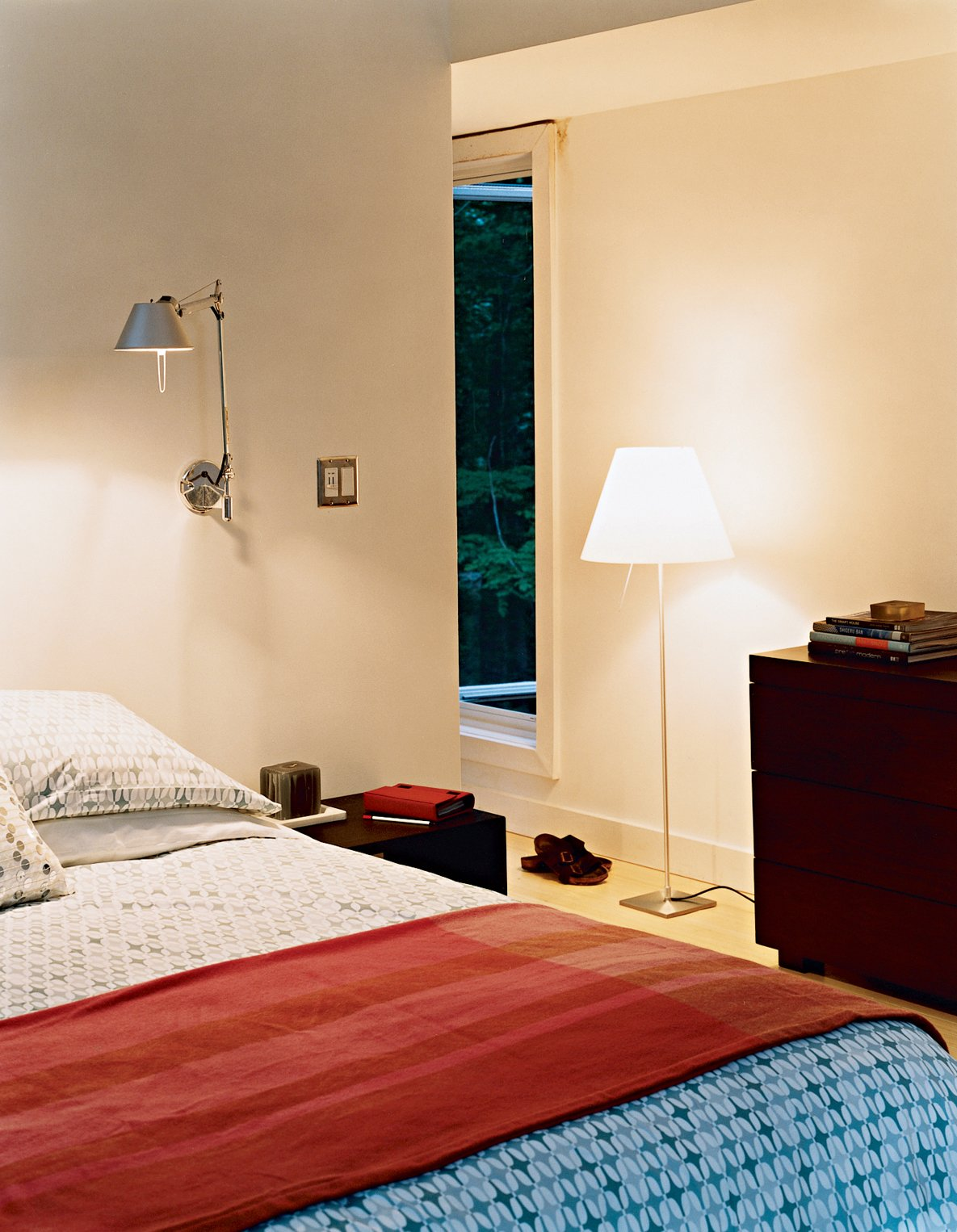The master bedroom has a number of windows in varying shapes and sizes, providing unique views to the woods outside. The bed, chest of drawers, side tables, and geometric linens are all from West Elm. The Tolomeo wall lamps are by Artemide.  Photo 6 of 12 in Prefab, Proven