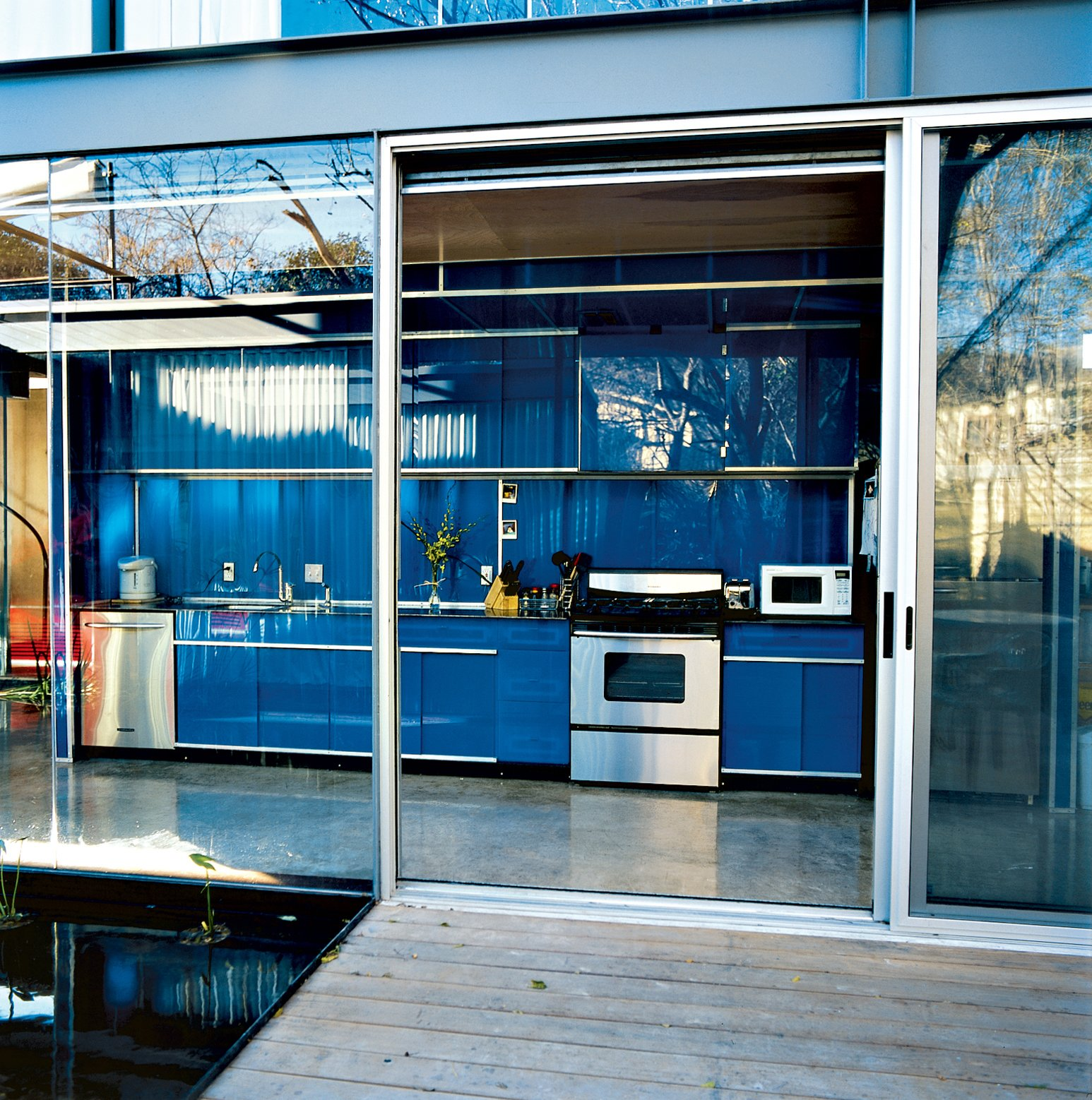 """Kitchen, Colorful Cabinet, and Concrete Floor The minimal aesthetic is seen in the galley-style kitchen, where the cabinets have no visible hinges   or knobs. The stainless steel  appliances are by KitchenAid.  Search """"where pigs fly"""" from Red, Wood, and Blue"""