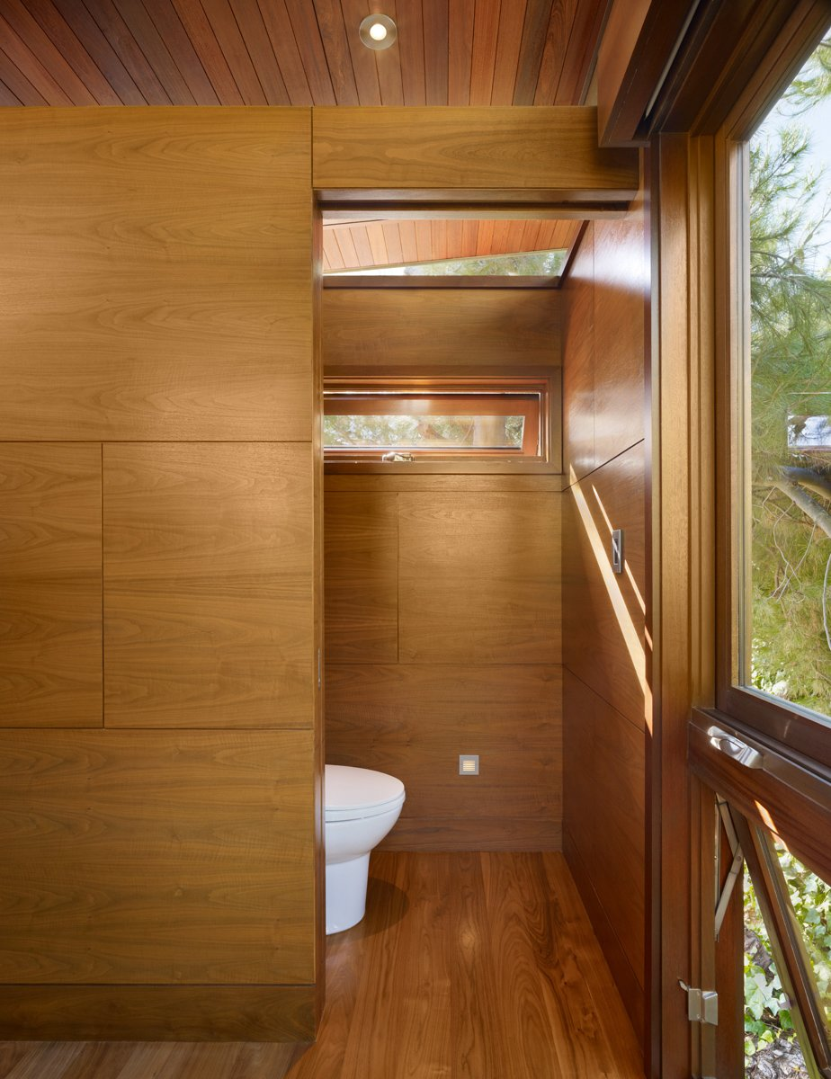 Bath Room and Medium Hardwood Floor The treehouse serves also as temporary guest quarters, with modern-day amenities like a daybed, a sink, a toilet, a small refrigerator, a fireplace and a microwave.  Photo 6 of 11 in An Atypical Tree House