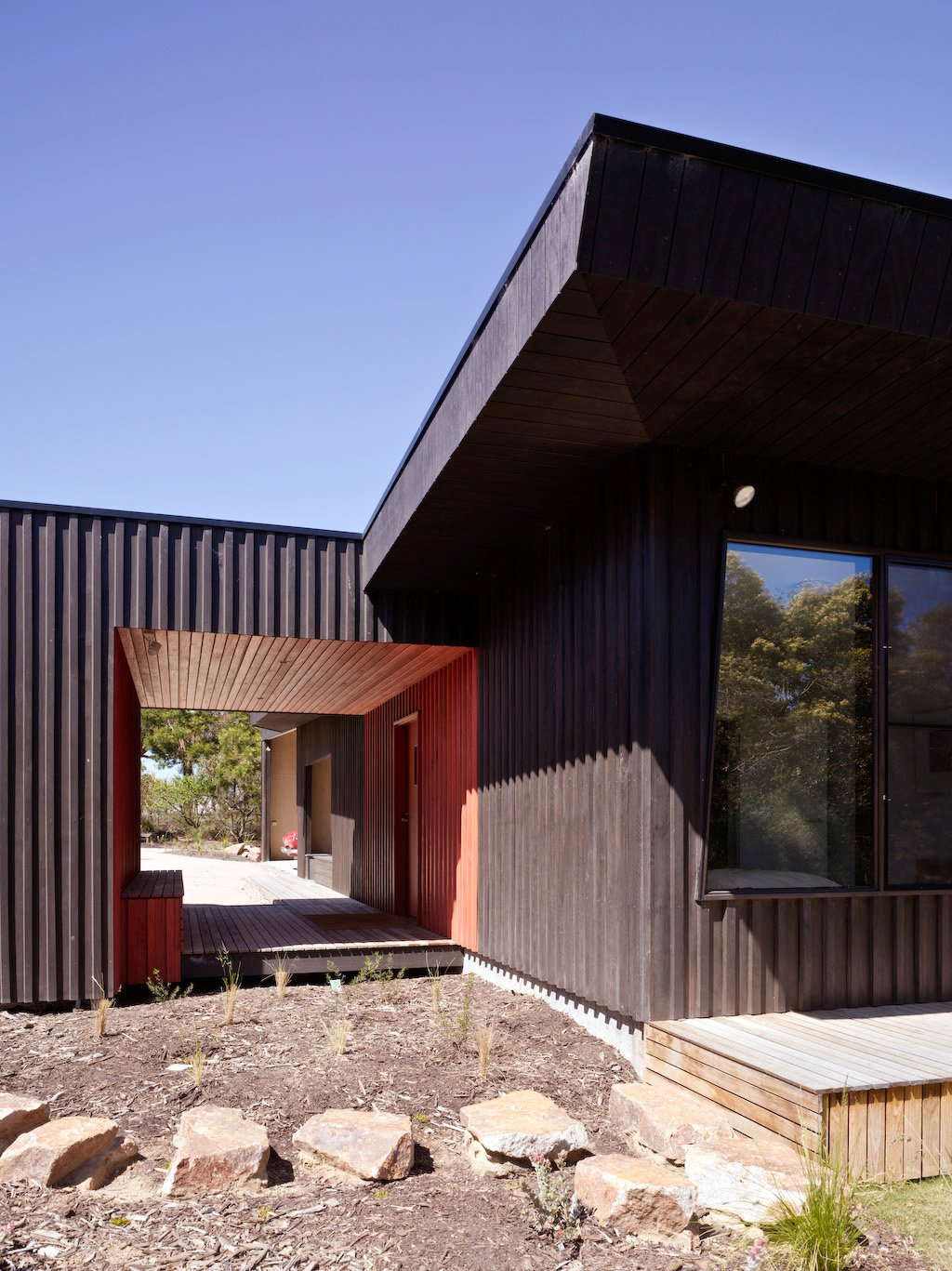 Outdoor, Side Yard, Hardscapes, Wood Patio, Porch, Deck, Boulders, and Walkways Courtyard House, Location: Somers Victoria Australia, Architect: Rowan Opat .Evolving from the notion of a series of outbuildings  on a greenfi eld site, principles of  passive solar design have informed this �courtyard  house�. The northern eaves respond directly to  shading becoming shallower in proportion to the  depth of space as experienced in the square plan.  As the dominant designed area, on this hectare  site, the courtyard both surrounds and is  surrounded by the house, creating a contained  space within an otherwise semi-rural block.  30+ All-Black Exterior Modern Homes by Zachary Edelson from Courtyard House by Rowan Opat