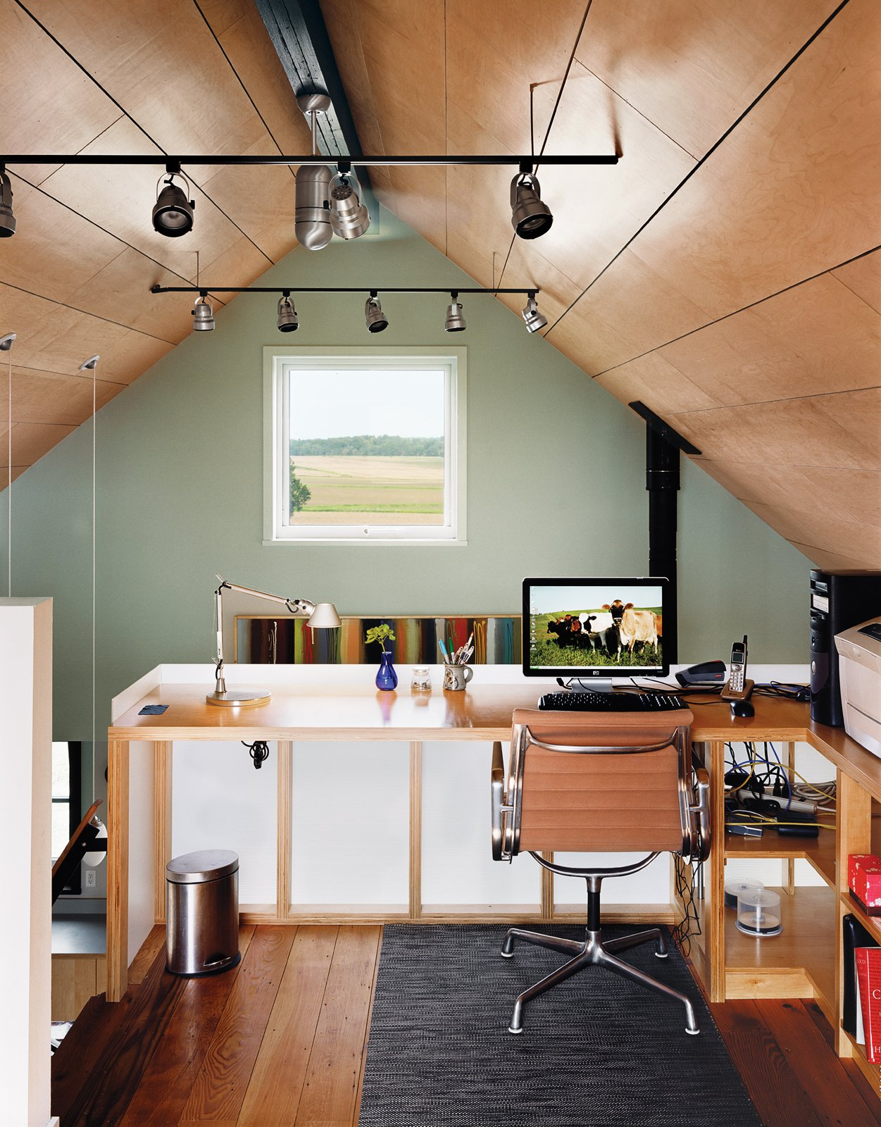 Office, Chair, Desk, and Medium Hardwood Floor From the office, a high window frames a view of the Moumings' fields.  Photo 8 of 10 in Farm Fresh