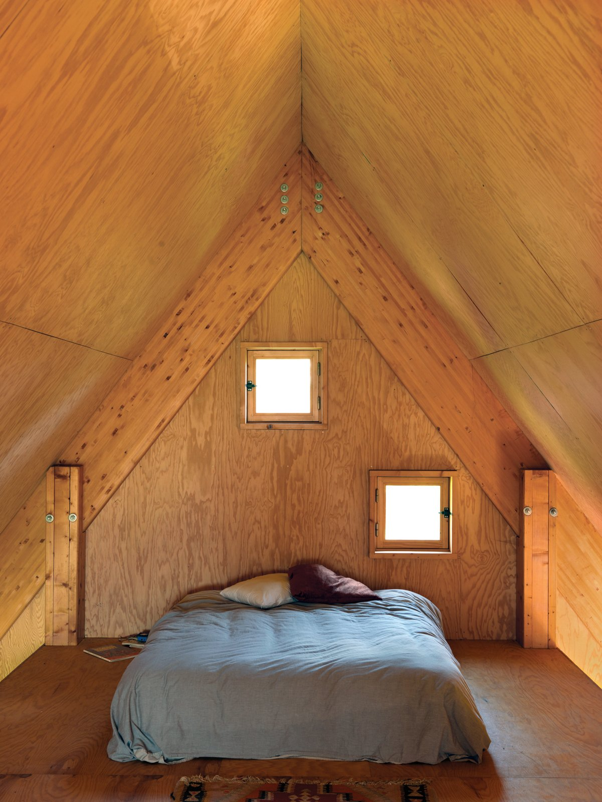 Bedroom and Bed In the third-floor bedroom, peekaboo windows offer a glimpse of the surrounding fields.  Photo 5 of 11 in Modern Wooden A-Frame Retreat in France
