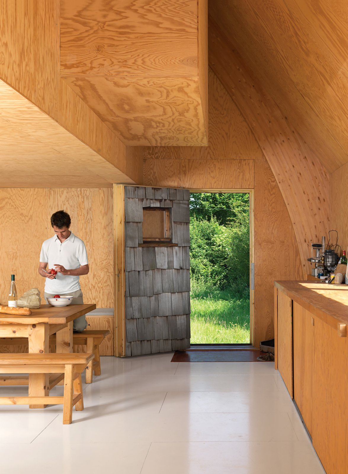 Kitchen and Wood Cabinet Built in 18 months on a budget of $105,000, this charming A-frame saves on costs with an interior lined with exposed plywood.    Photo 9 of 11 in Modern Wooden A-Frame Retreat in France