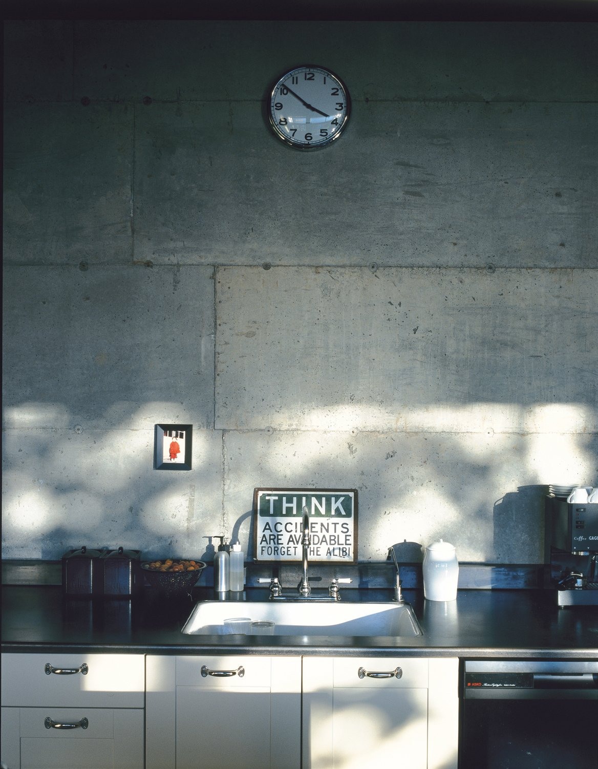 Kitchen, White Cabinet, and Concrete Backsplashe The kitchen countertops are covered in a thicker version of the same mild steel that clads the house and coated with beeswax to protect from scratches and stains.  Photo 1 of 6 in Brand-New Secondhand