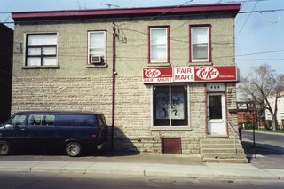 The building, as it appeared when the owners bought it in 2001. Behind the brick wall at left, the architect and owners found another window, which was reopened. The building has held a confectionery, a general store, a rooming house and a post office.
