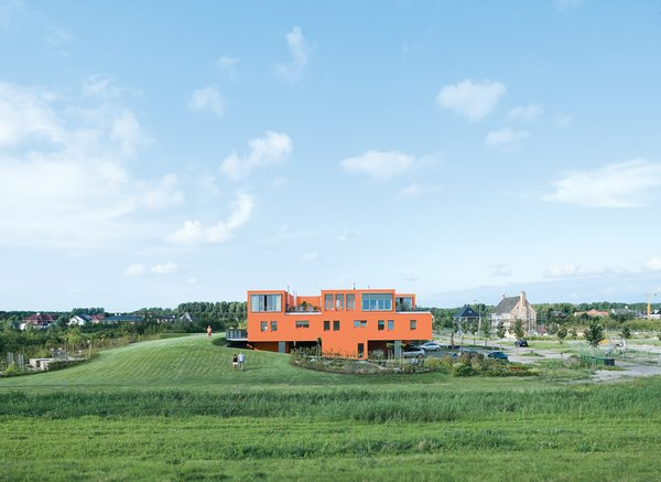 Seen here from the south, Villa van Vijven's orange facade is meant to mimic the tiled rooftops of Holland's country buildings, while the building's horizontal pull echoes the flat landscape. The second-floor living rooms look out on the 4,200-square-foot communal garden, one of only two shared spaces in the whole community. Bob Krone, Koos Sweringa, and Marianne Schram stroll the grounds.  Examples of Modern Communal Living by Megan Hamaker from Modern Communal Living in the Netherlands
