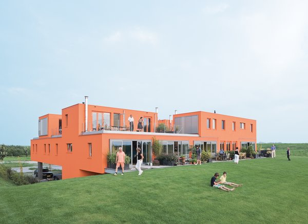 This eye-catching villa in the Netherlands, designed by Next Architects, proves that you can go big and go home as well. While some homes feature hints of color, the Villa van Vijven structure garners well-deserved attention thanks to its warm orange facade that is meant to mimic the tiled rooftops of Holland's country buildings. The orange of the exterior also carries over into the communal entrance beneath the building, offset by natural elements such as stones adjacent to the entryway.