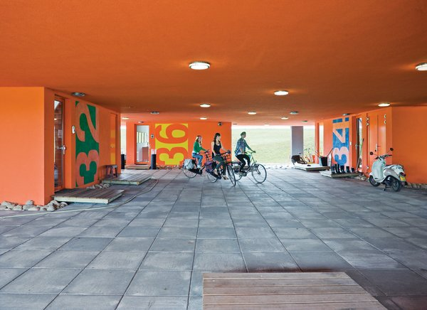 """The communal entrance beneath the building is known as the """"public square""""; sisters Tessa and Anne Bouwmeester and a friend set off on their bikes."""