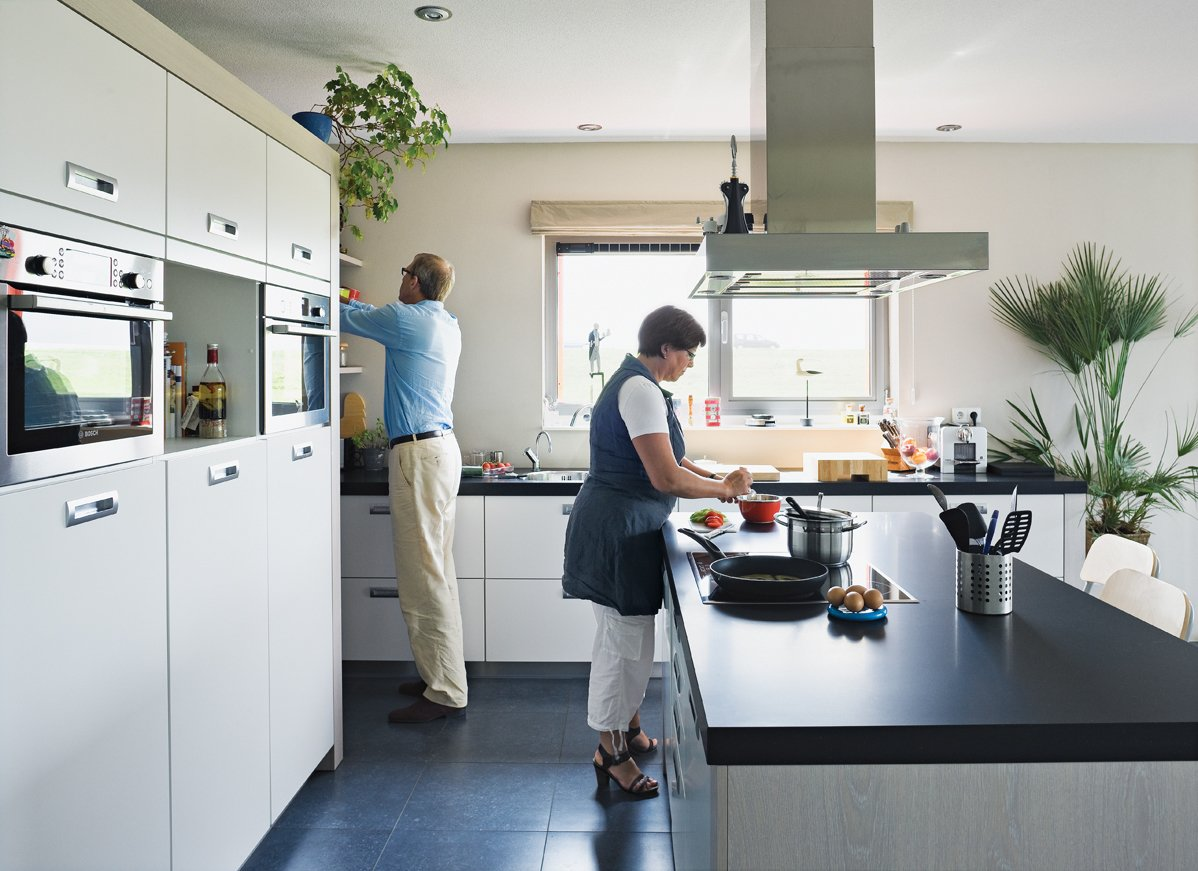 Kitchen, Range Hood, Cooktops, Wall Oven, Microwave, White Cabinet, and Wood Cabinet Koos Sweringa and Marianne Schram putter in the kitchen.  Photo 11 of 22 in Modern Communal Living in the Netherlands