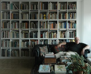 Architect Peter Eisenman reclines at home surrounded by his massive library.