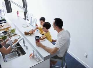 The family shares a meal at the counter in the kitchen.